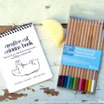 """Creative Cat Coloring Book"" with watercolor pencils and art sponge."