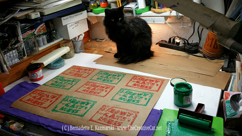 Hamlet supervises the test sheets of Meowy Cat's Mess wrapping paper.