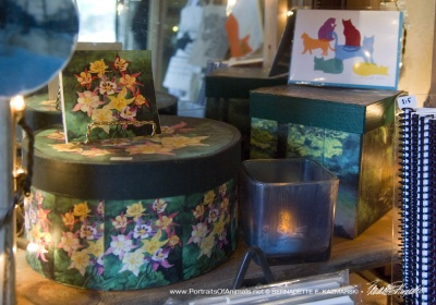 The green display with keepsake boxes, tiles, votives, and hand-printed note cards.